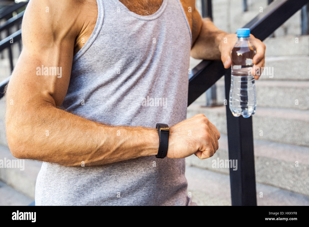 Sportsman with bottle of water is resting and checking his smart watch after running. fitness, sport, exercising Stock Photo