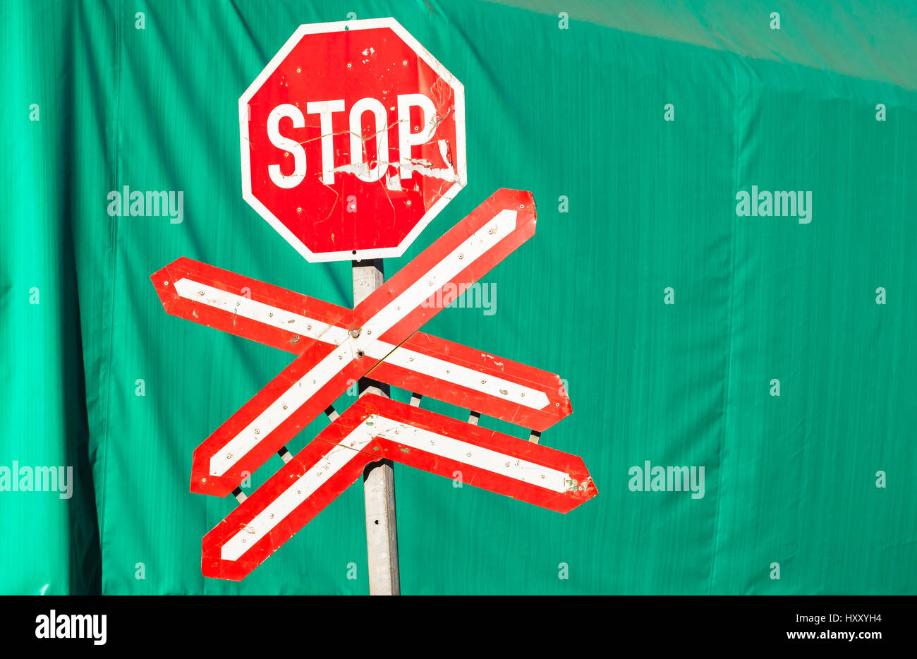 Stop Sign Green Background abstract contrasts train line intersection. - Stock Image