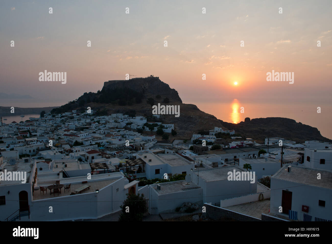 sunrise with the village of Lindos and the acropolis in the foreground, Lindos, Rhodos, Greece - Stock Image