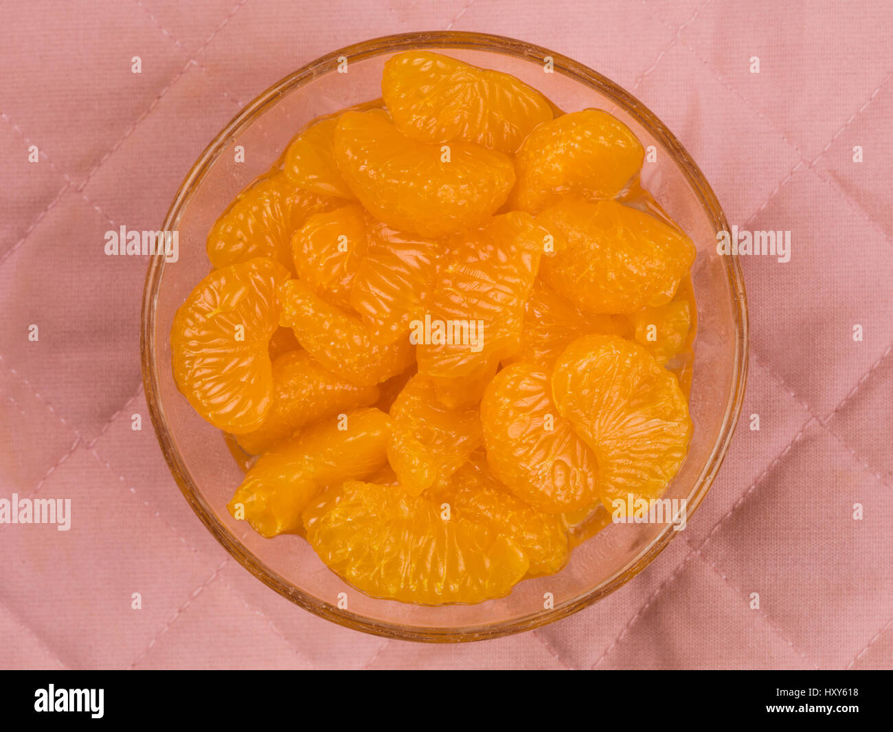 Mandarin Orange Segments in a Bowl Against a Pink Background - Stock Image