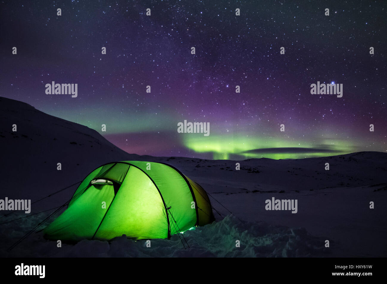 Tenting under the aurora Stock Photo