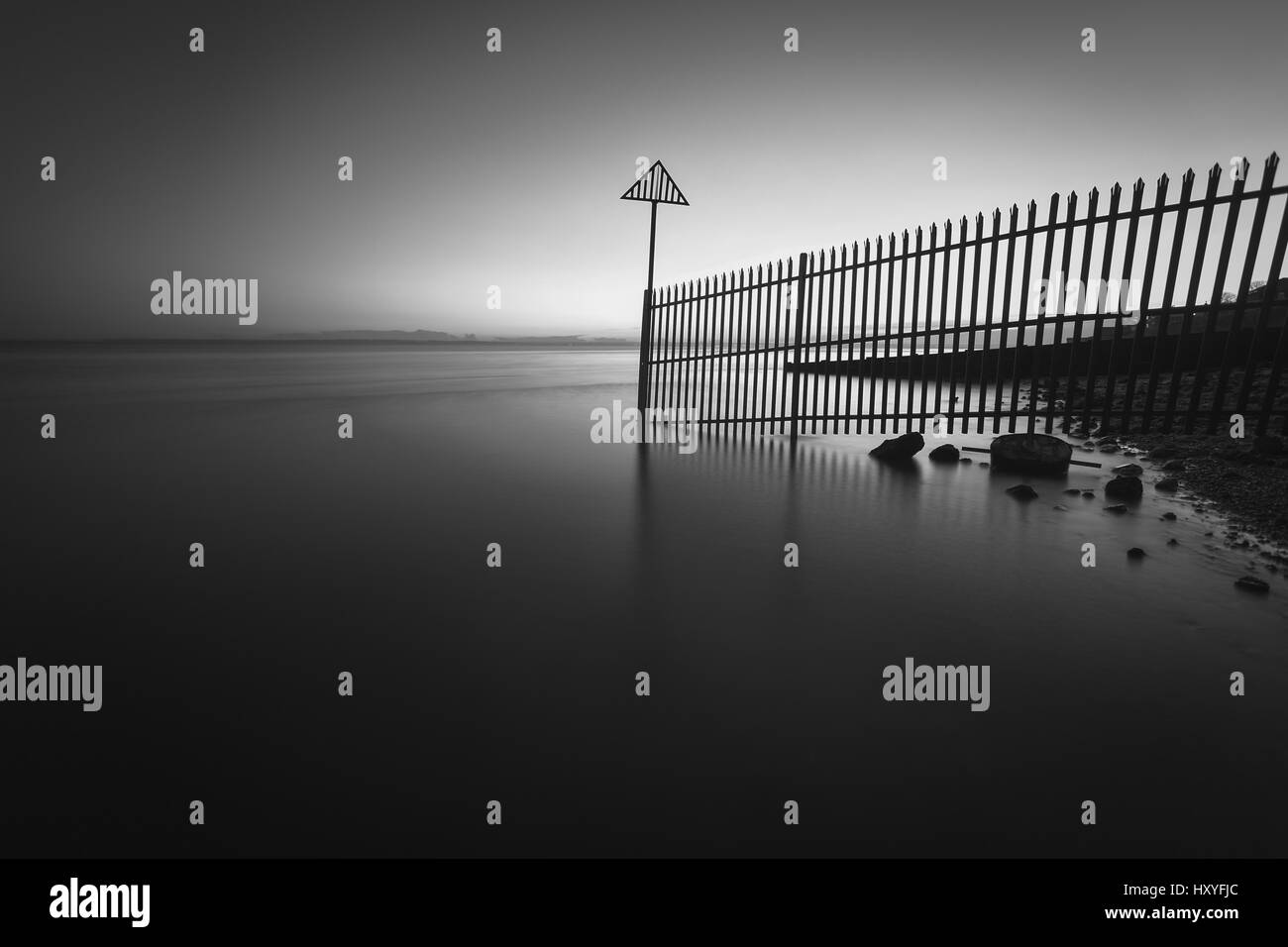 Fence barrier partially submerged in the sea Stock Photo