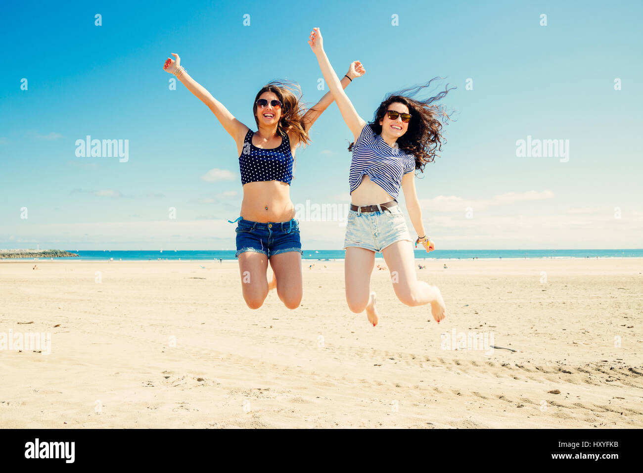 Happy and funny girl friends jumping on the beach, Some blur on legs beacuse of movement - Stock Image