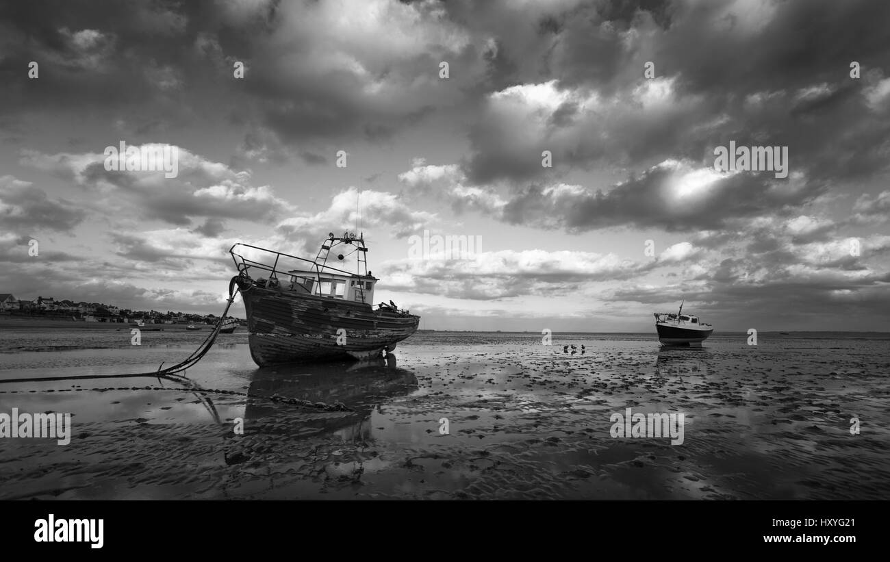 Boats at low tide in Southend on Sea with birds passing Stock Photo