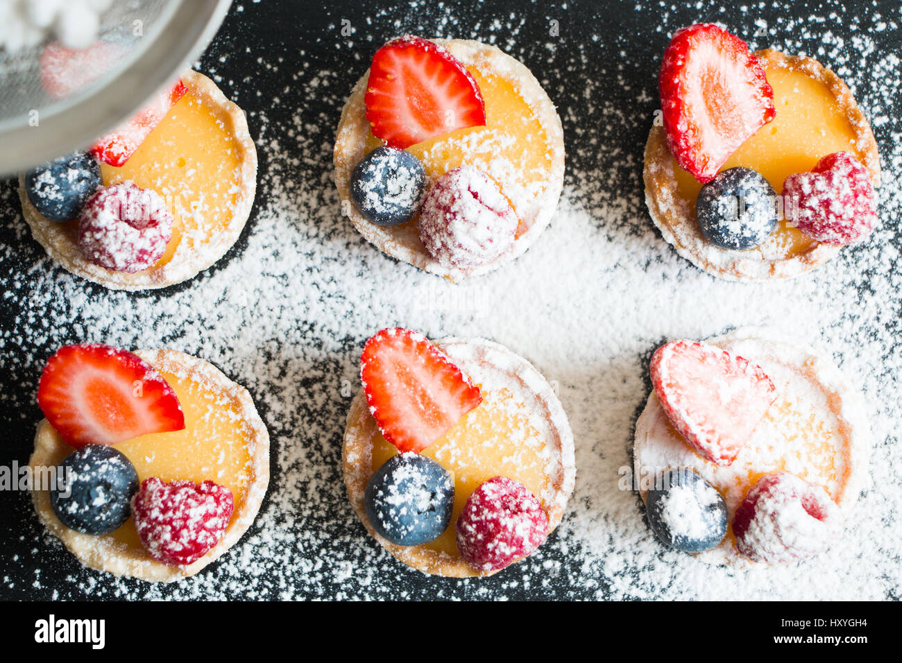 Small tarts of cream and fresh berries with icing sugar - Stock Image