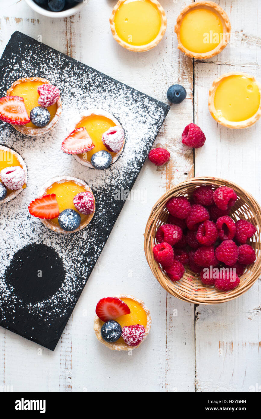 Preparing small pastry tartlets filled with vainila cream and fresh berries in a rustic white wooden table - Stock Image