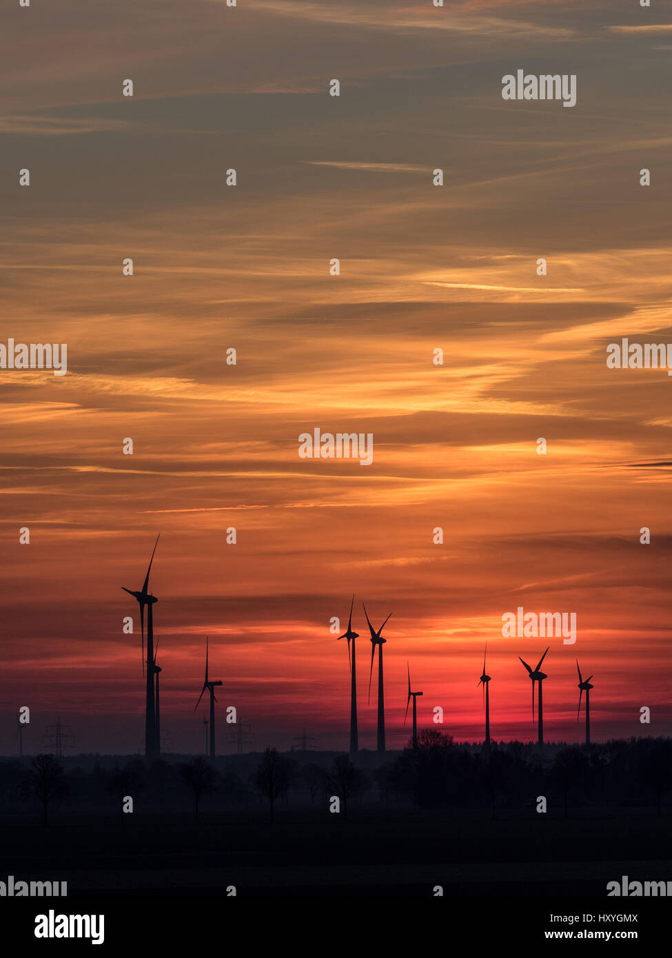 Wind power plants at sundown with colorful clouds and sky - Stock Image