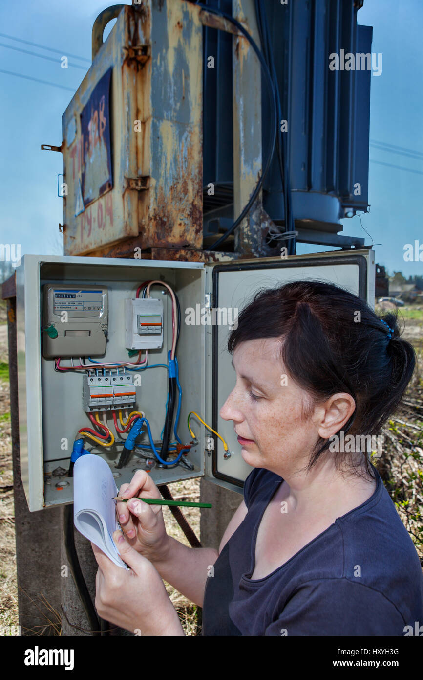 Woman electrician engineer inspecting electric counter equipment in distribution fuse box, electricity switchgear Stock Photo