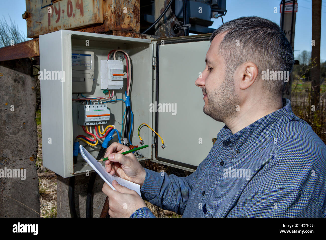 Outdoor electric substation, electrician engineer Writing Reading Of electricity Meter On Clipboard. Stock Photo