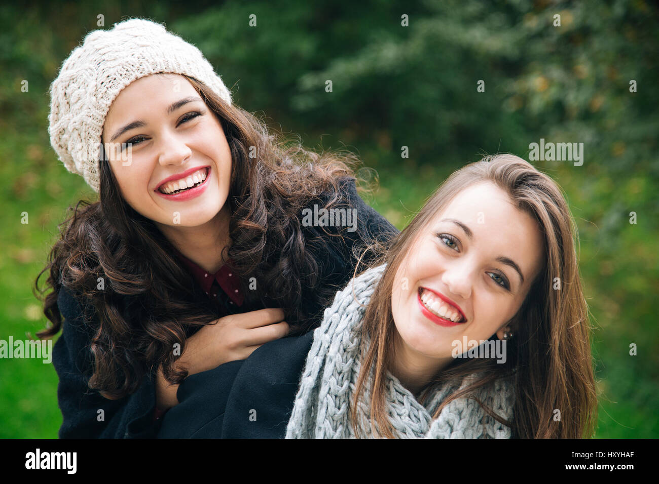Cute best friend girls a piggyback in winter or fall outdoors stock image