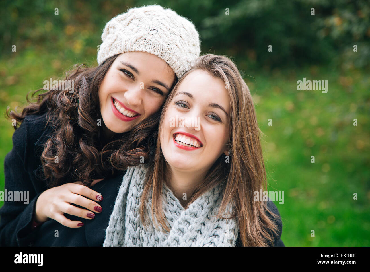 Cute best friend girls a piggyback in winter outdoors - Stock Image