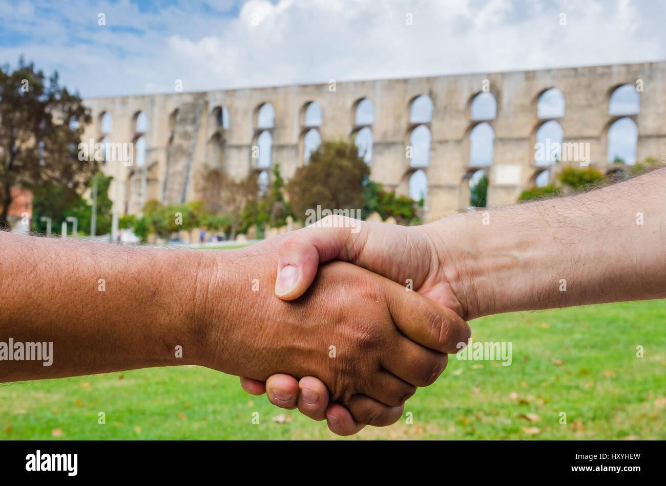 Closeup of people shaking hands. Amoreira Aqueduct in Town of Elvas Alentejo Region. Portugal, Europe - Stock Image