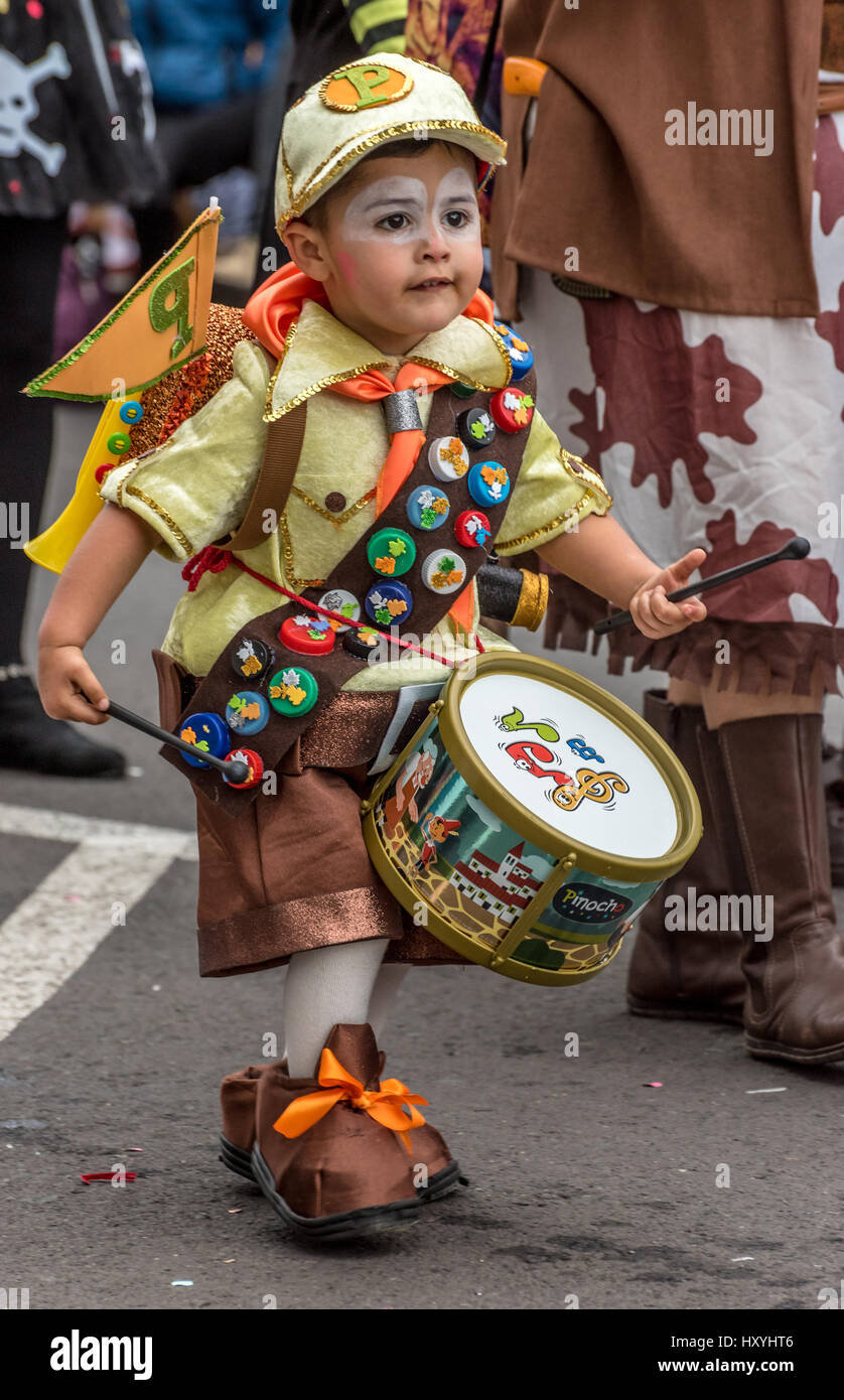 Little boy, playing a toy drum, in very elaborate boy scout/pioneer costume in the Tenerife carnival parade - Stock Image
