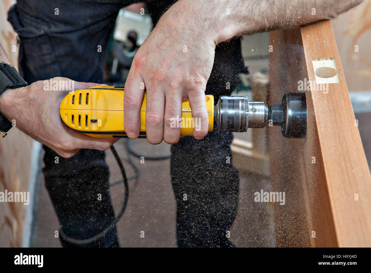 Hands woodworker with yellow electric drill, boring large hole of door lock, using hole saw drill bits, sawdust - Stock Image