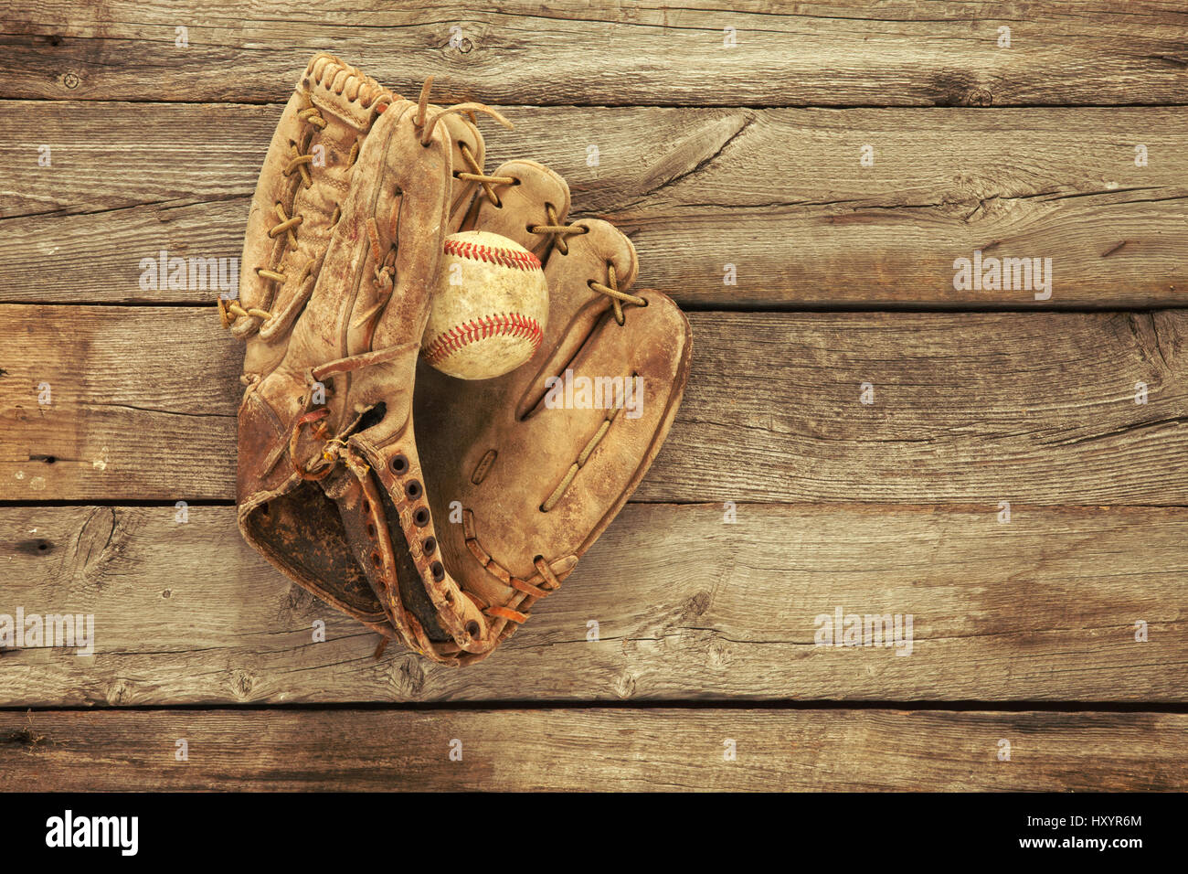 vintage baseball mitt and ball on grungy rough wood background