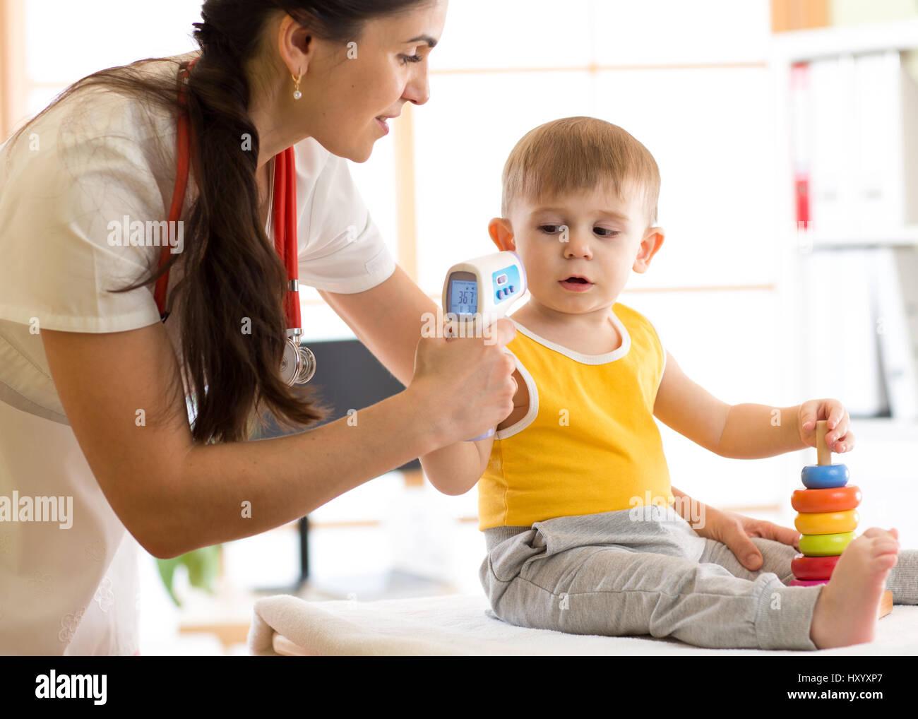 doctor measuring temperature cute kid - Stock Image