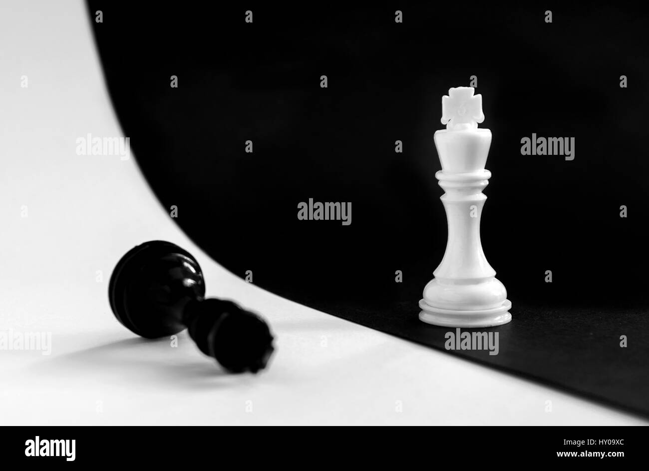 King and Queen chess game pieces on a black and white board - Stock Image