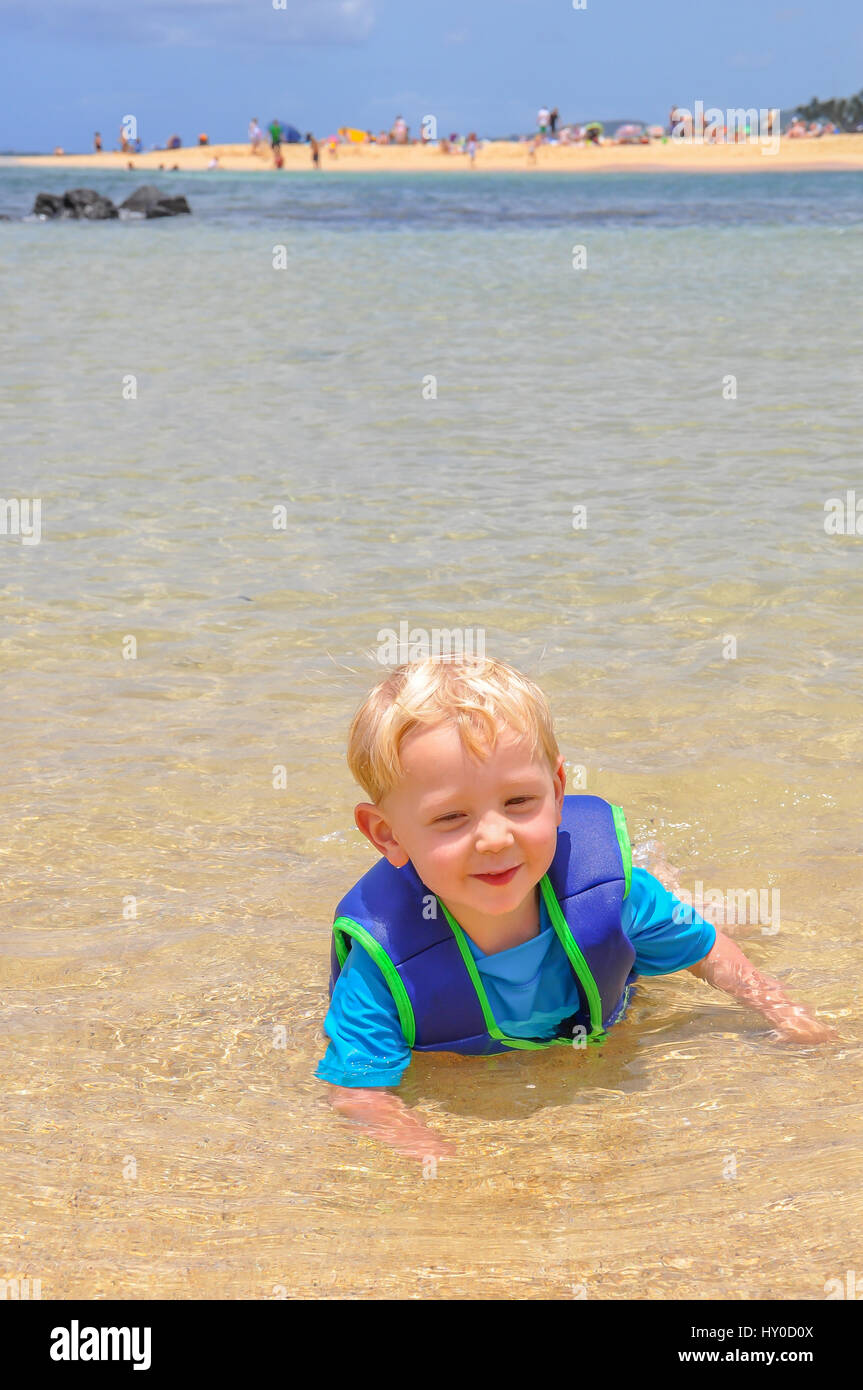 A blond toddler plays in the calm, clear water at Popul Beach State Park in Poipu on a family vacation in Kauai, - Stock Image