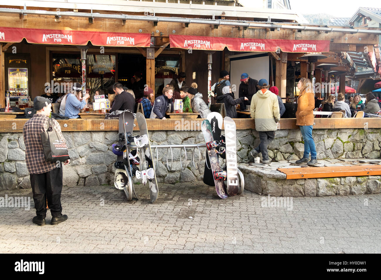 Tourists eat on the patio of a sidewalk cafe in the Whistler ski resort.  Whistler BC, Canada. - Stock Image