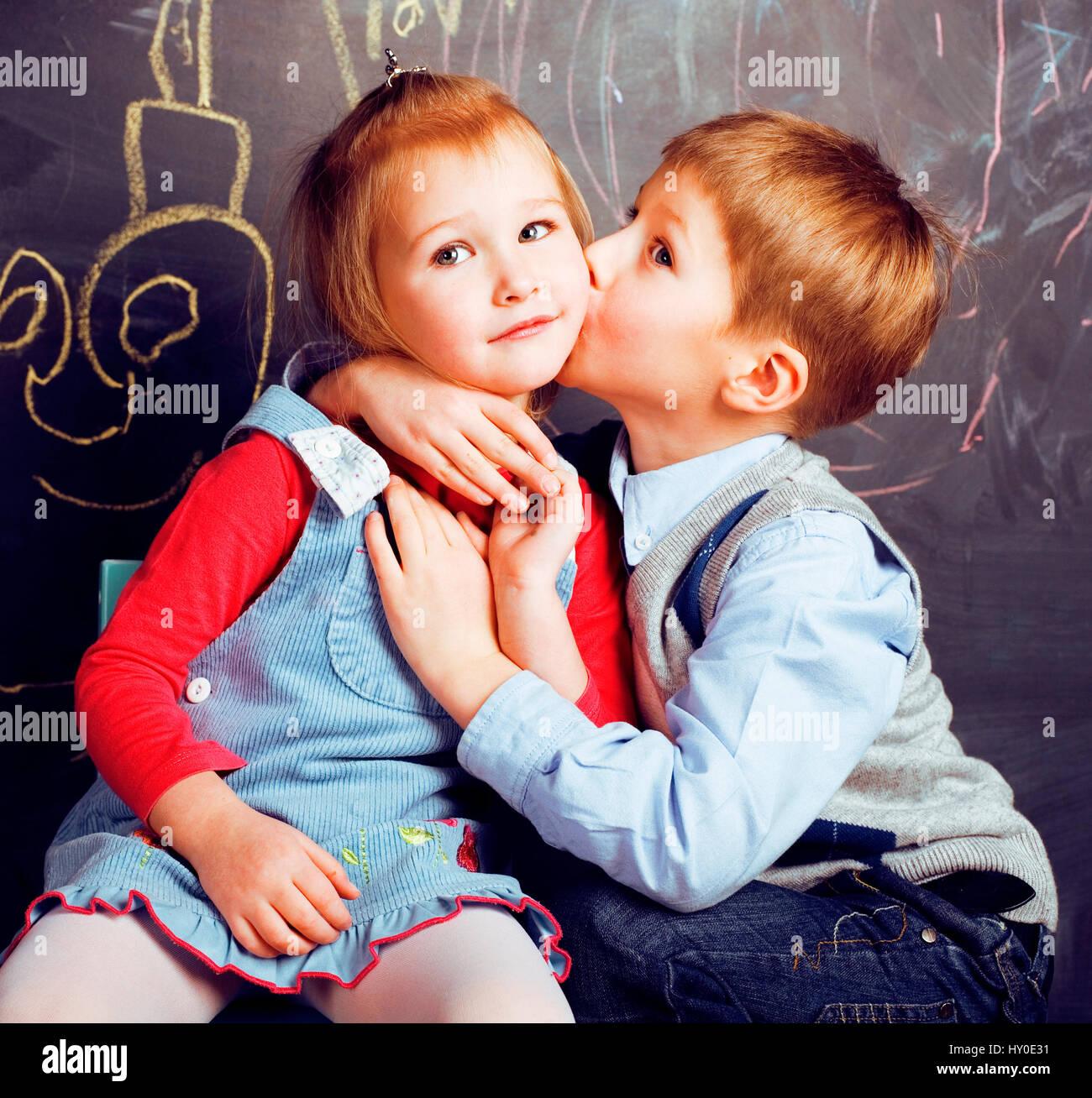 little cute boy kissing blonde girl in classroom at blackboard
