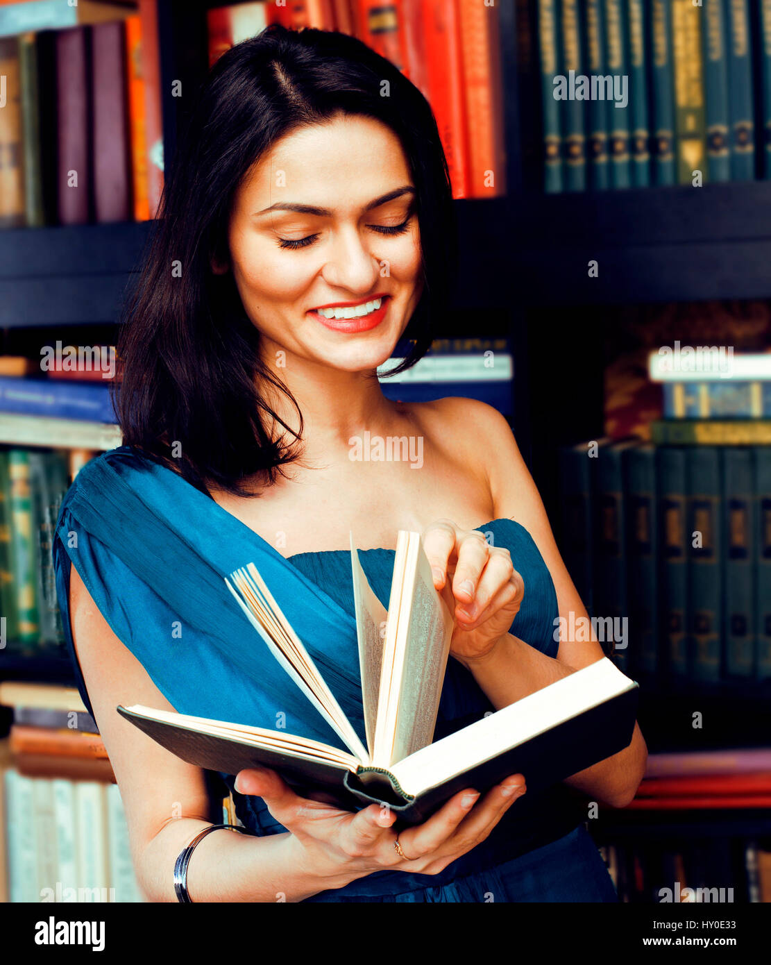 young teen brunette muslim girl in library among books emotional close up  bookwarm, lifestyle smiling people concept
