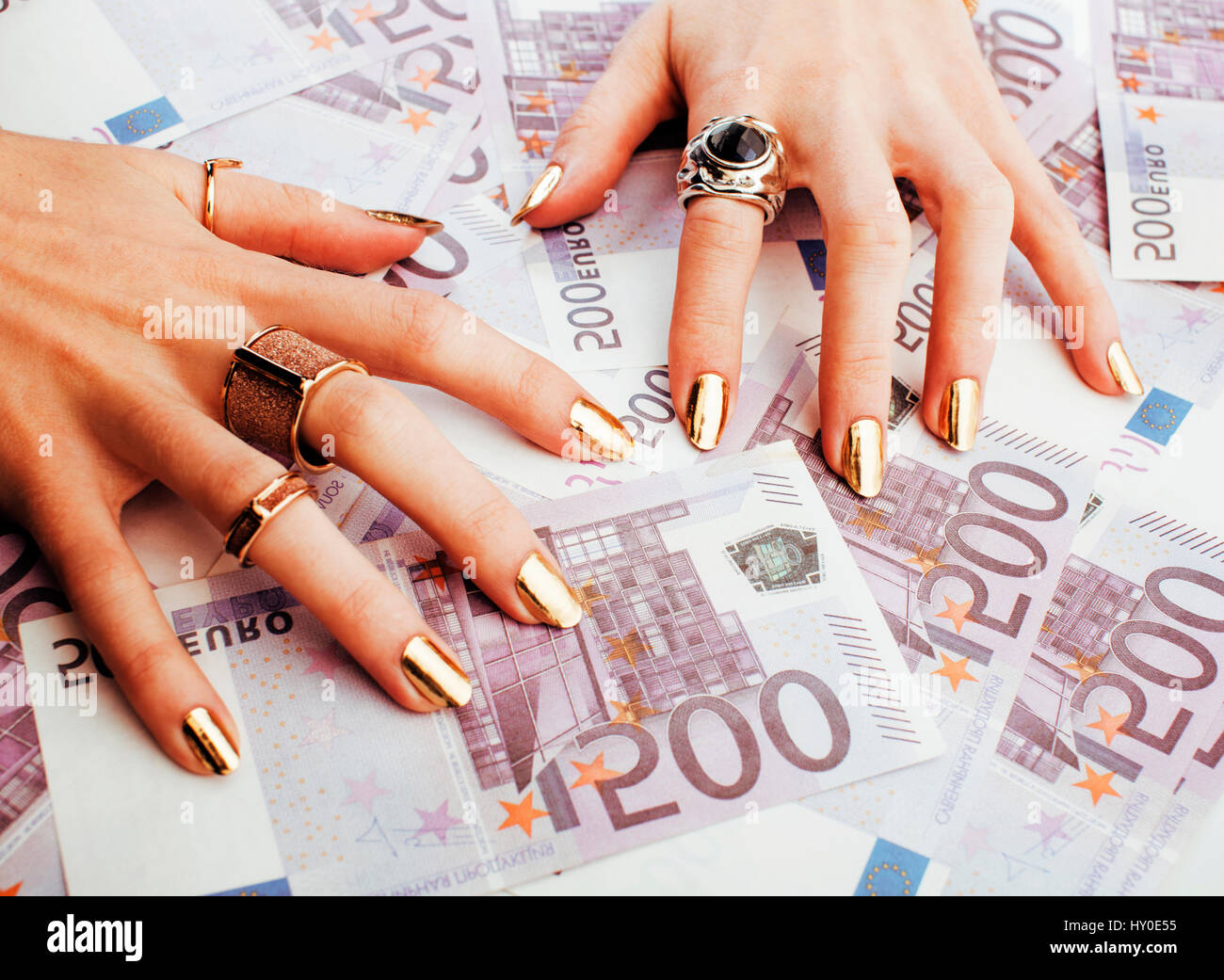 hands of rich woman with golden manicure and many jewelry rings ...