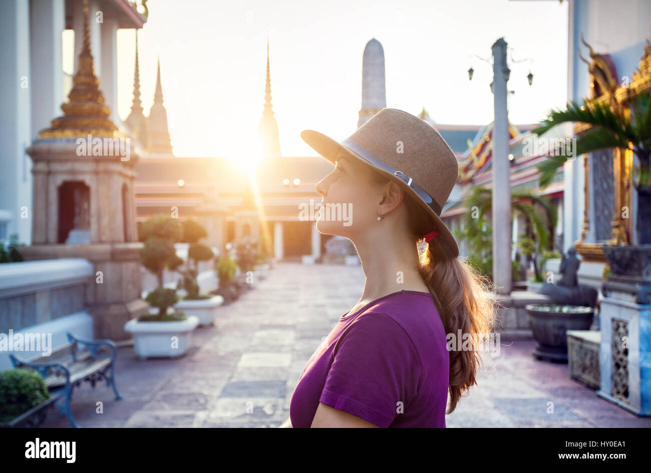Beautiful tourist woman in the hat and purple t-shirt in Wat Pho temple at sunset in Bangkok, Thailand. - Stock Image