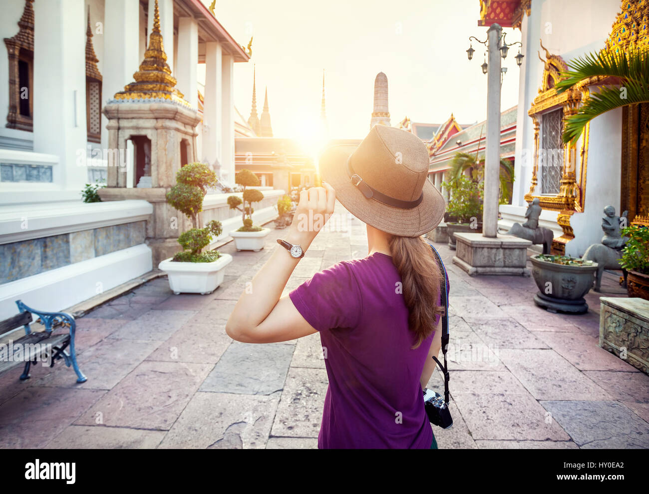 Tourist woman in the hat and purple t-shirt with photo camera in Wat Pho temple at sunset in Bangkok, Thailand - Stock Image