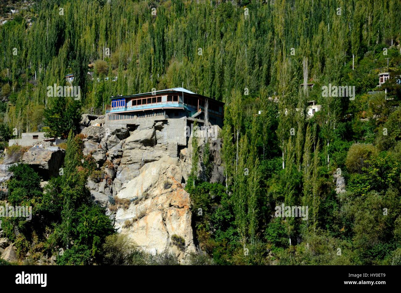 A building stands on top of a rocky ledge in Hunza Valley Pakistan - Stock Image