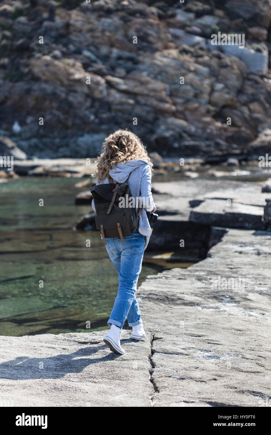 Full length portrait of blond woman tourist with khaki backpack wearing jeans and gray jacket walking on rock ribbed Stock Photo