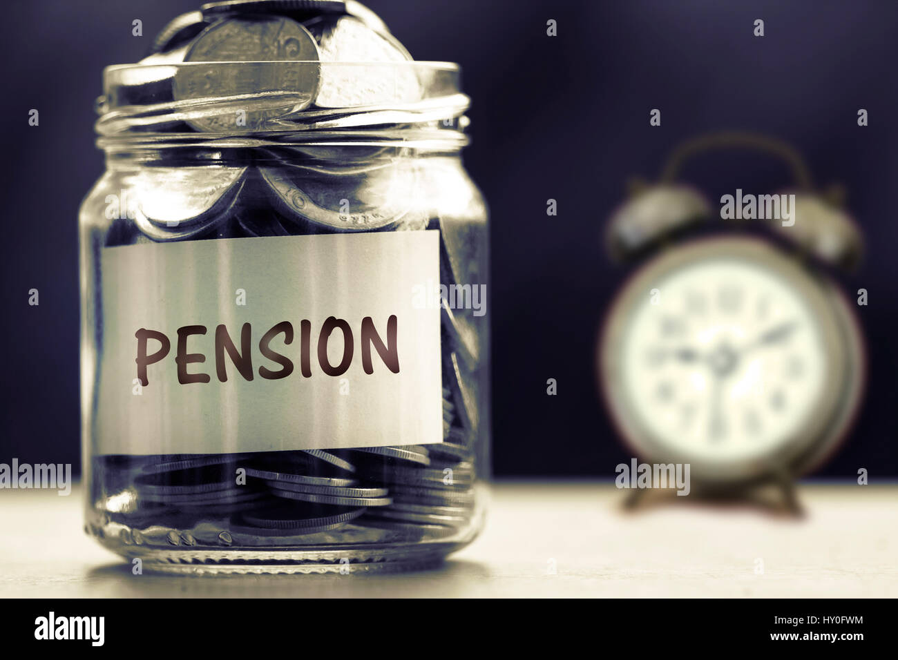 Close up Coins in glass jar for giving and pension concept , dark retro color tone - Stock Image