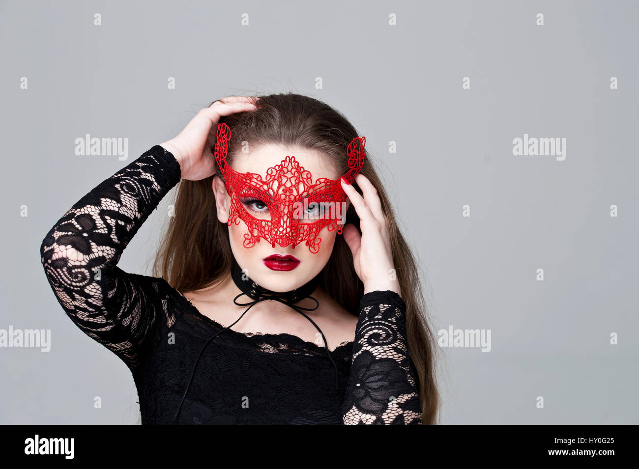 25a69ec8e7 Young woman with long fair hair wearing a red lace mask and a black dress  with