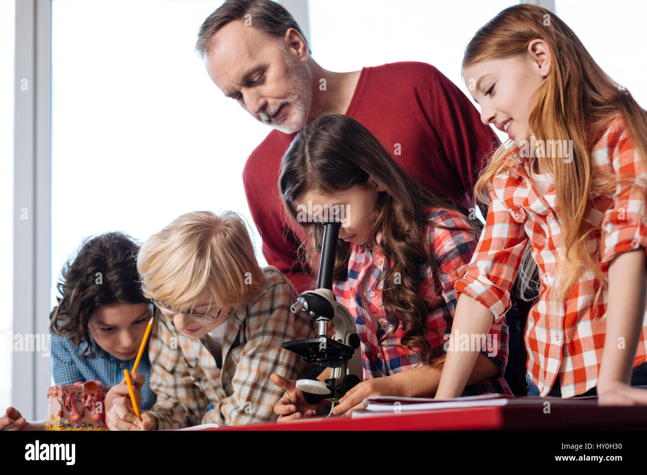 Admirable professional teacher assisting his students - Stock Image
