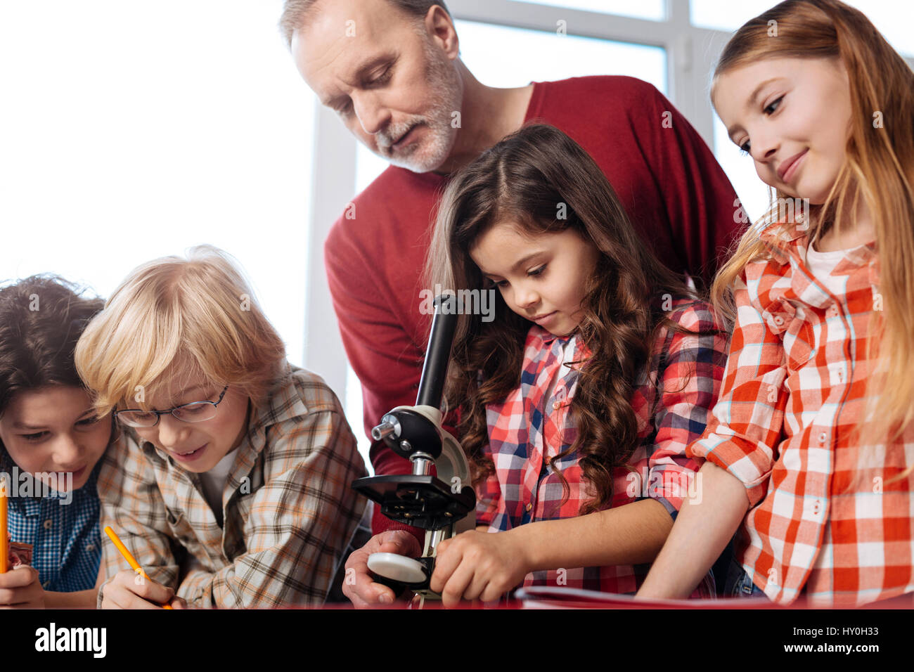 Attentive teacher monitoring the experiment - Stock Image