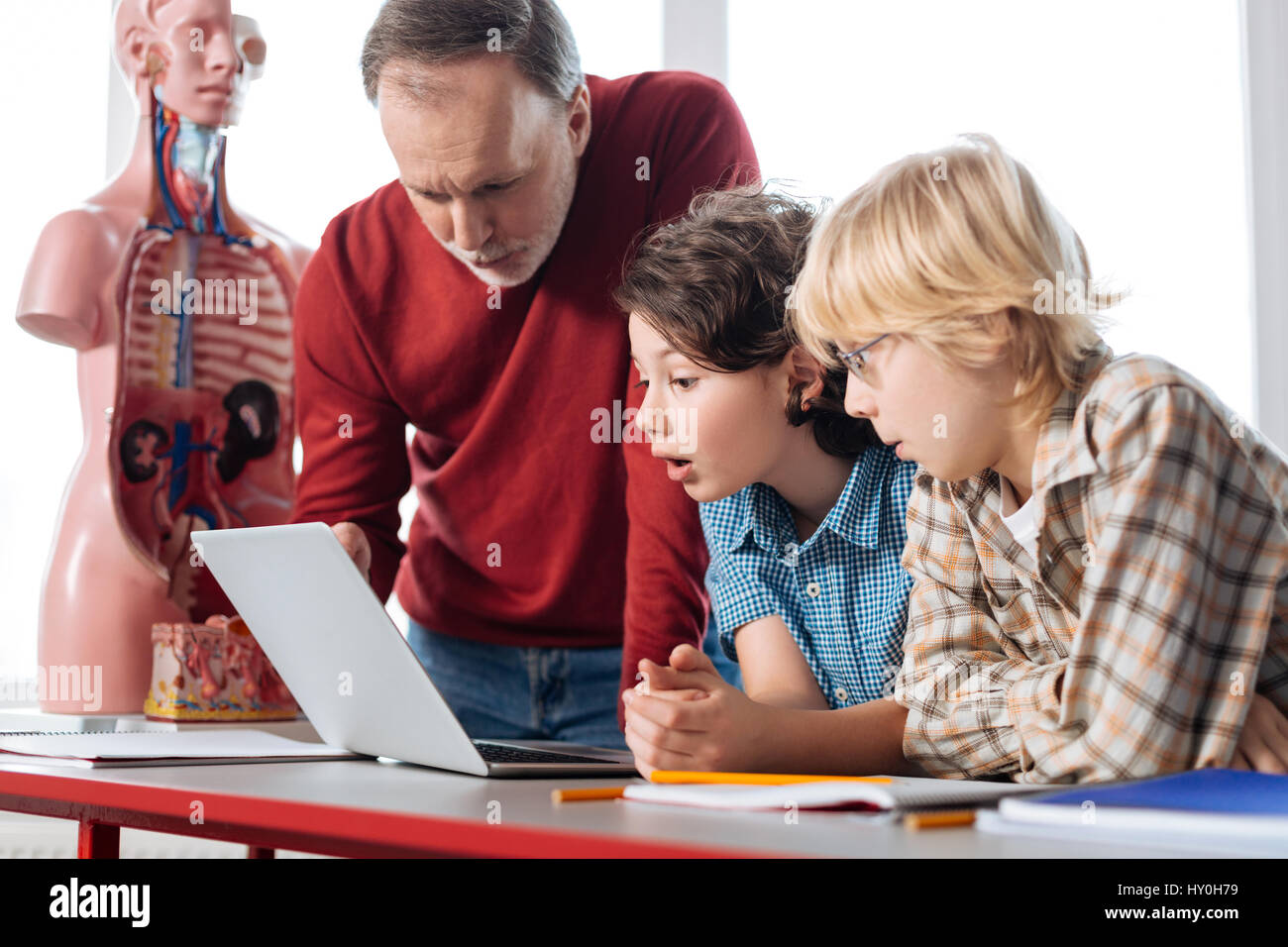 Excited determined students showing results to their teacher - Stock Image
