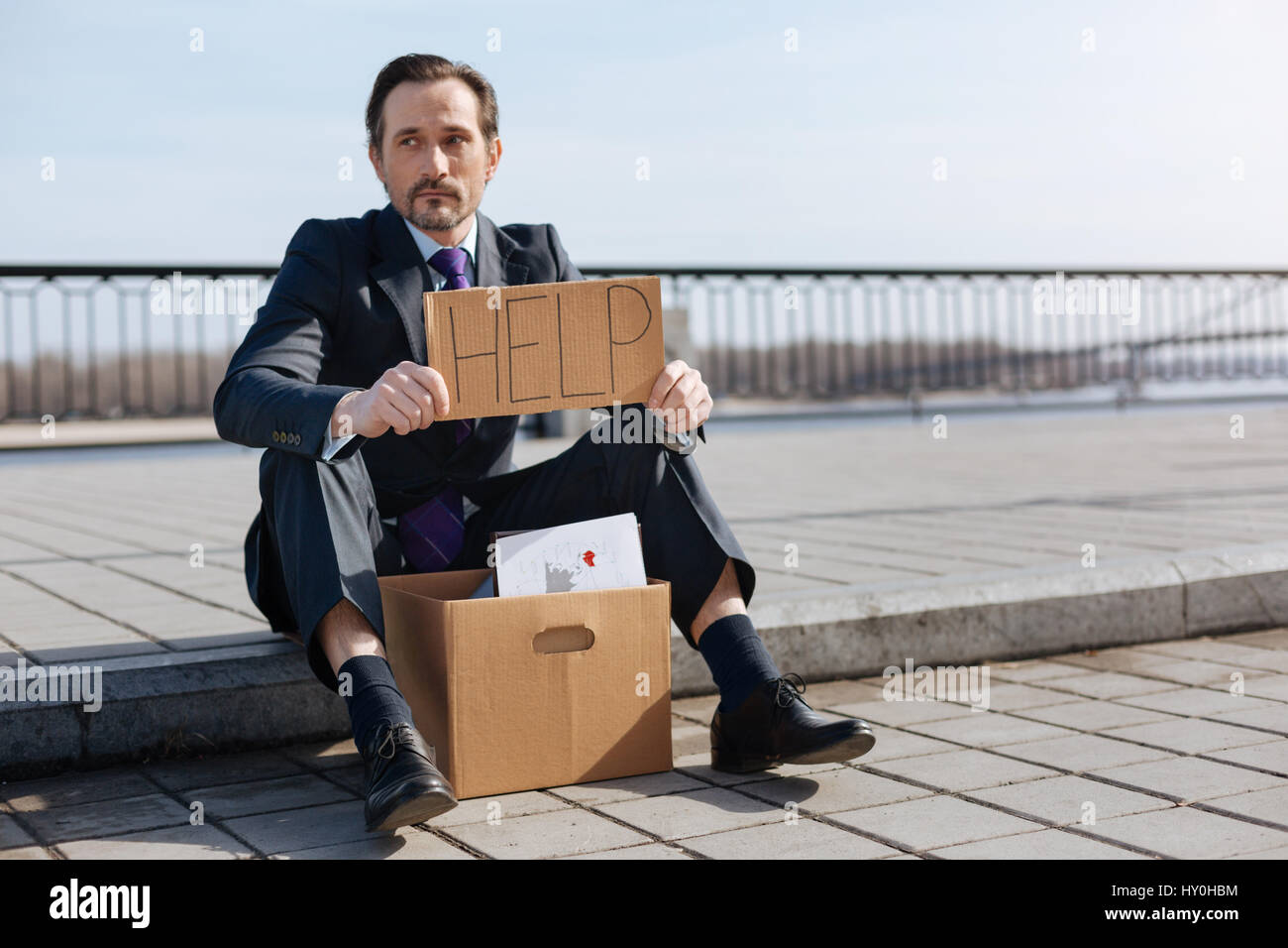 Jobless male person asking for help - Stock Image