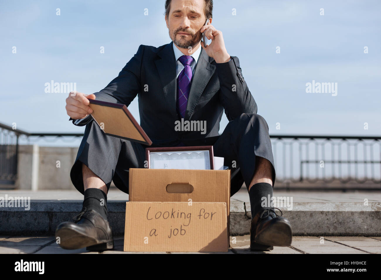 Upset jobless male holding his reward - Stock Image