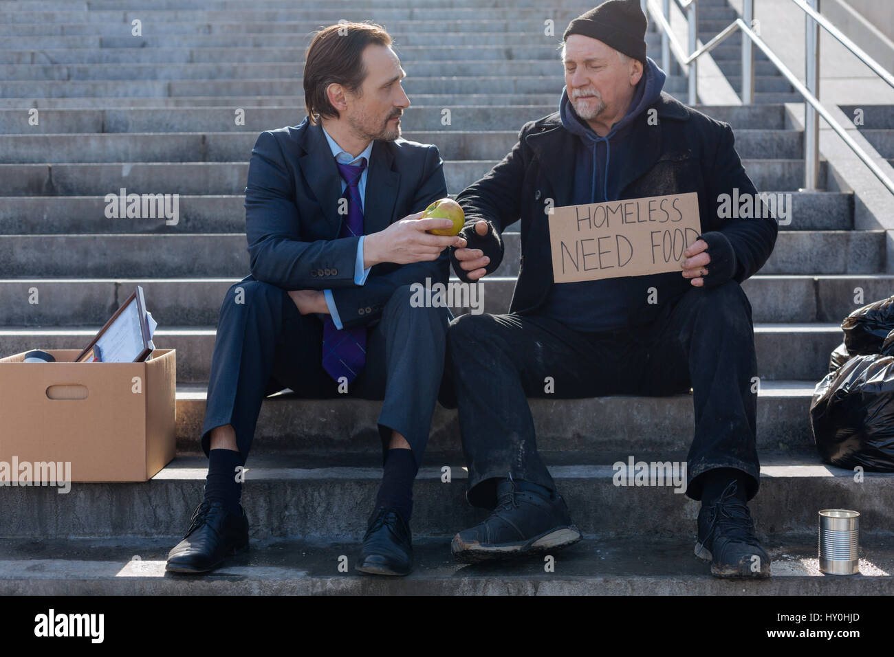 Jobless and homeless sitting next to each other - Stock Image