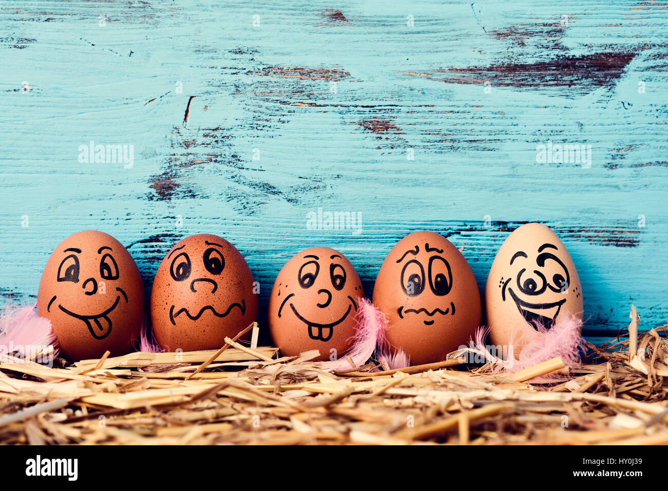 Some Brown Eggs With Funny Faces On A Pile Of Straw Against Blue Rustic Wooden Background Blank Space Above Them