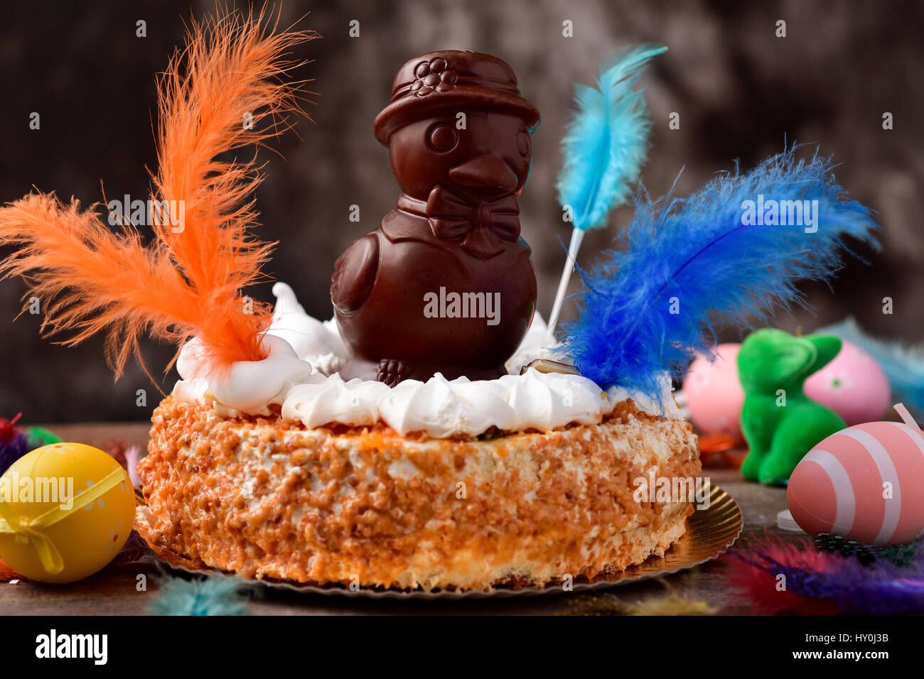 a mona de pascua, a cake eaten in Spain on Easter Monday, topped with a chocolate chick, on a rustic wooden surface Stock Photo