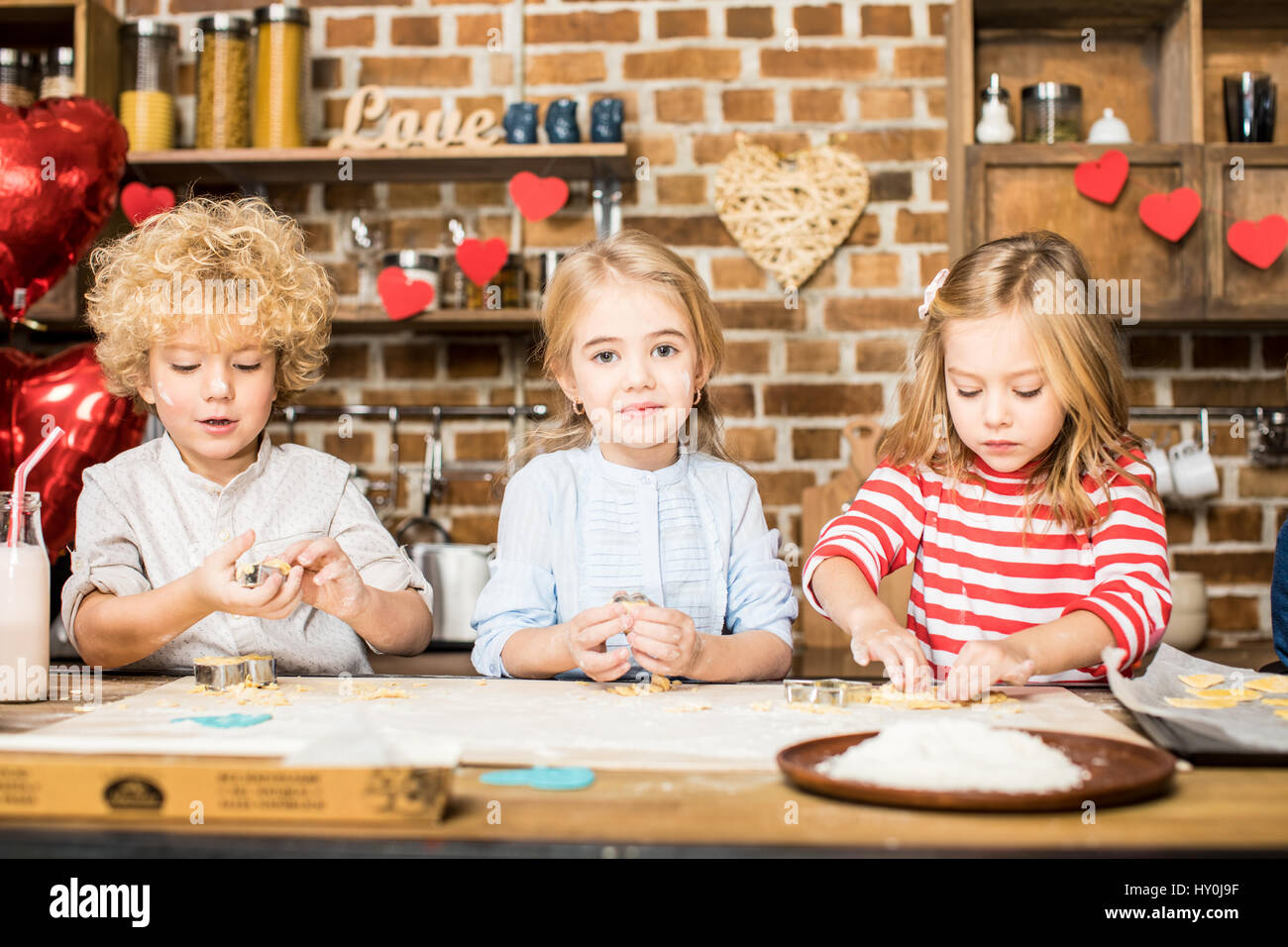 Three adorable little children cooking biscuits from unbaked dough - Stock Image