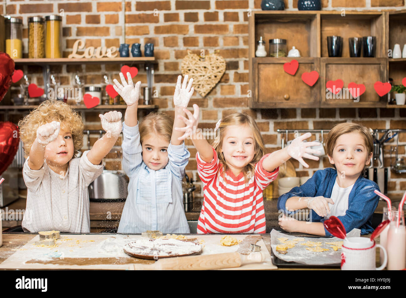 Adorable happy children cooking biscuits and showing hands in flour - Stock Image