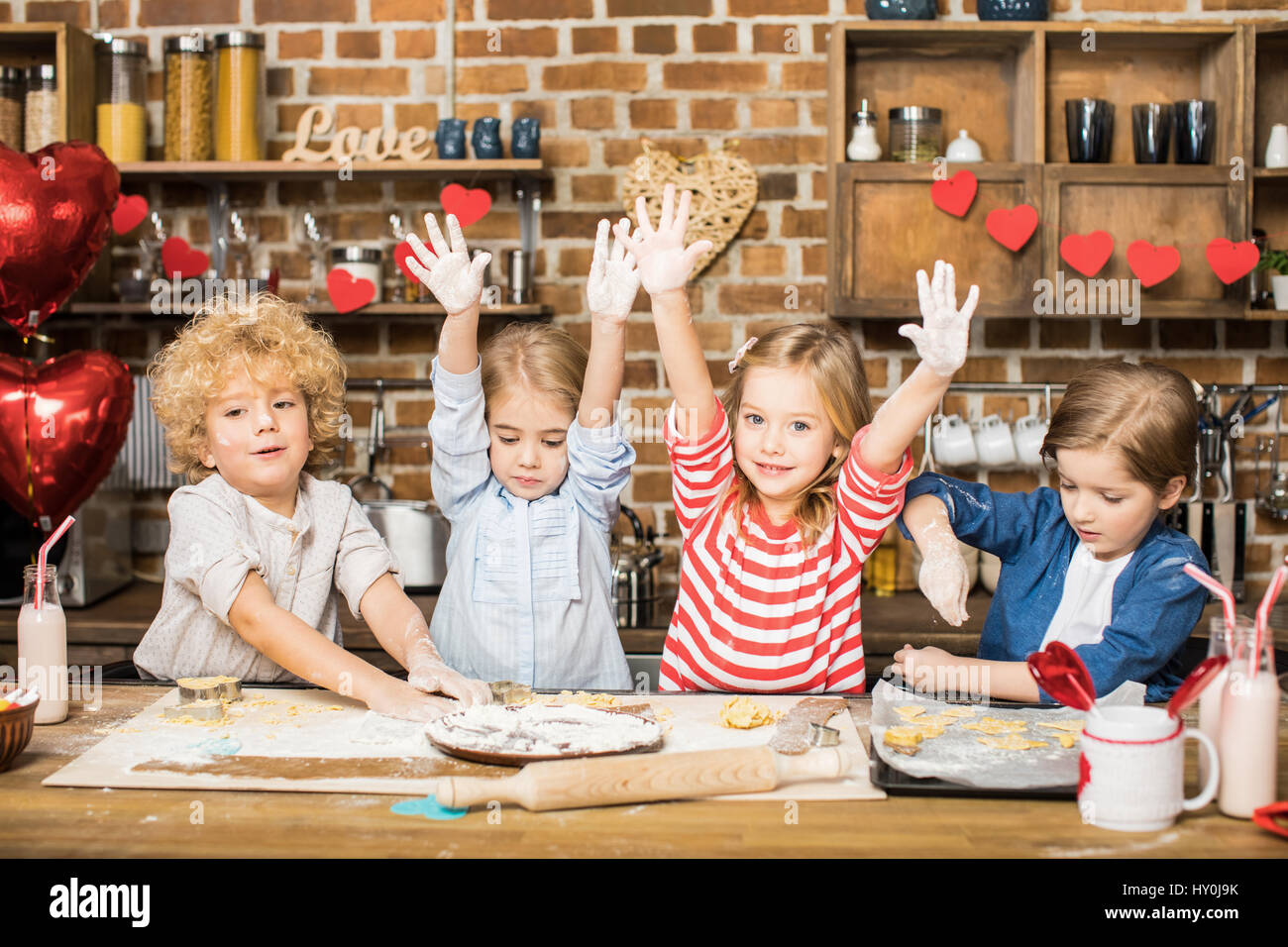 Four cute little children cooking biscuits and showing hands in flour - Stock Image