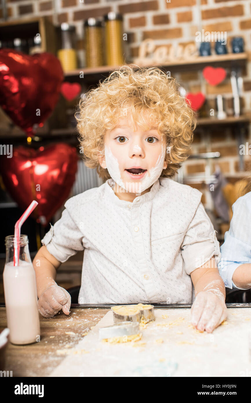 Portrait of exited little boy with flour-streaked face making cookies - Stock Image