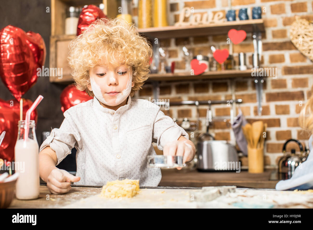 Portrait of little boy with flour-streaked face making cookies - Stock Image