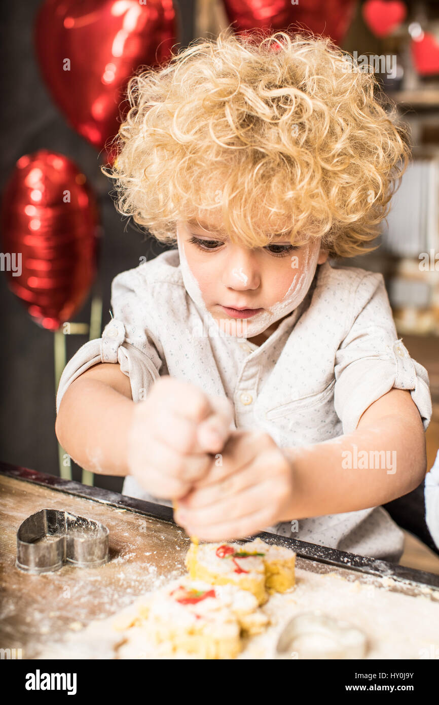 Portrait of curly little boy icing cookies for party - Stock Image