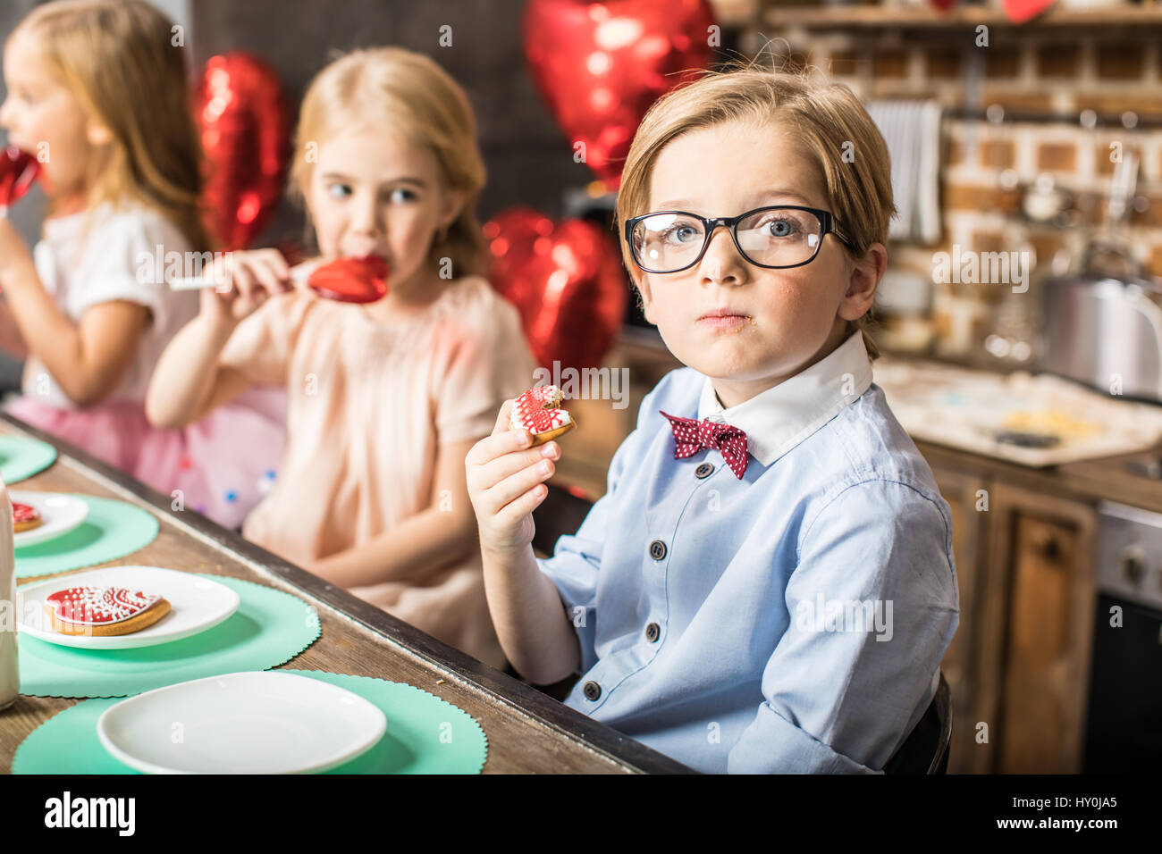 Stylish boy in eyeglasses eating cookie at birthday party - Stock Image