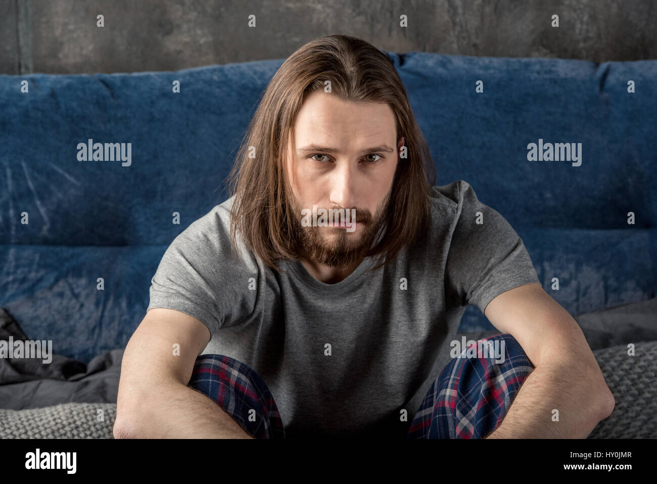 Serious bearded man sitting in bed and looking at camera - Stock Image