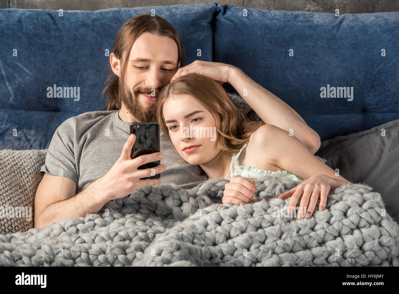Young couple lying in bed and holding remote control - Stock Image