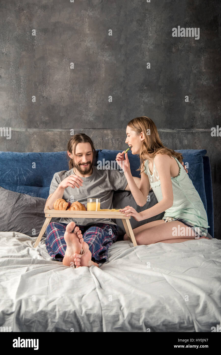 Young happy couple has breakfast in bed - Stock Image